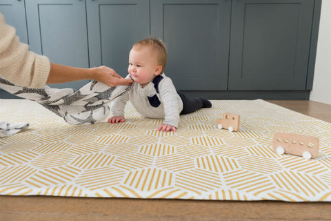 Happy baby tummy time on a luxury Totter + Tumble playmat