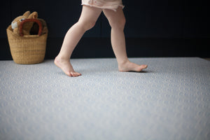 Toddler walking across Totter + Tumble's Seafarer iron blue playmat subtle pattern to fit in with your home interior
