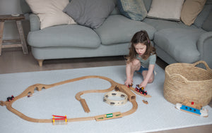 Playing with trains on Totter + Tumble's light greenish grey Wanderer playmat
