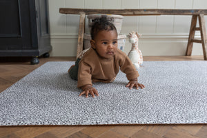 Totter and tumble new collection neutral leopard print the Trailblazer. A ditsy, monochrome leopard pattern soft padded baby playmat paired with a sophisticated grey background with a hint of lilac undertones. Baby playing tummy time playmat for all floors, stylish home interiors