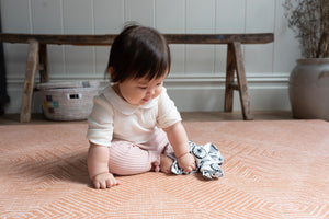 totter and tumble beautiful stylish padded foam play mat for babies and toddlers. Enabling stylish interiors for the family home this printed rug for babies to play on is made from a luxury, soft padded memory foam in a soft terracotta colour The Captain aztec pattern. Reversible, stylish playmat paired with monochrome ditsy leopard print The Trailblazer. Baby playing tots tumbling