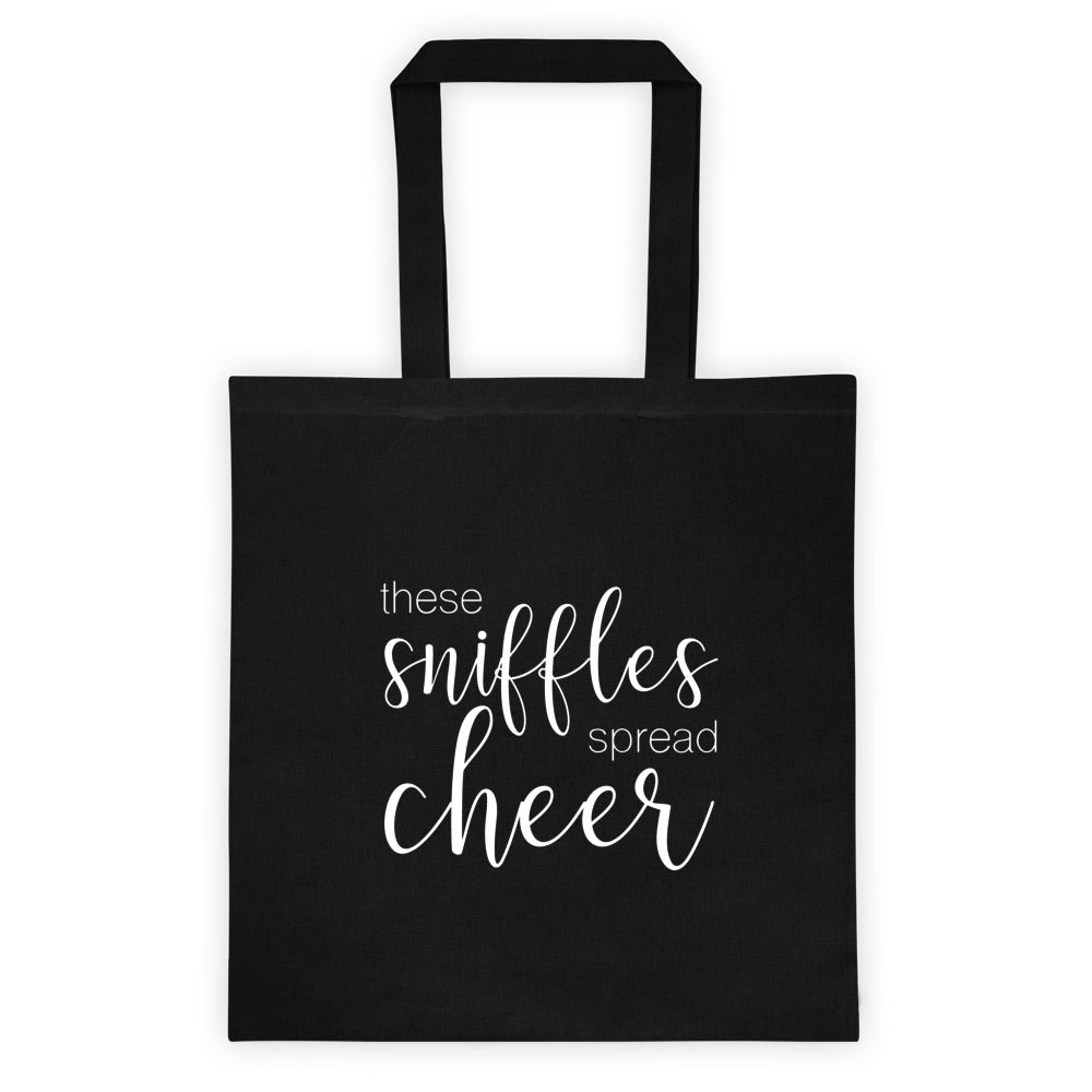 black tote bag with these sniffles spread cheer in script