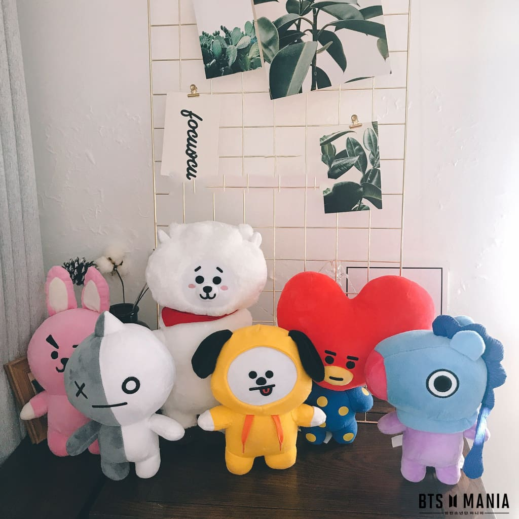a group of stuffed animals sitting next to a teddy bear