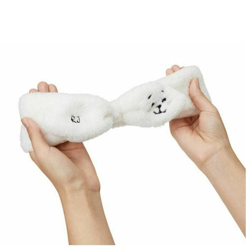 a hand holding a white cat with its mouth open