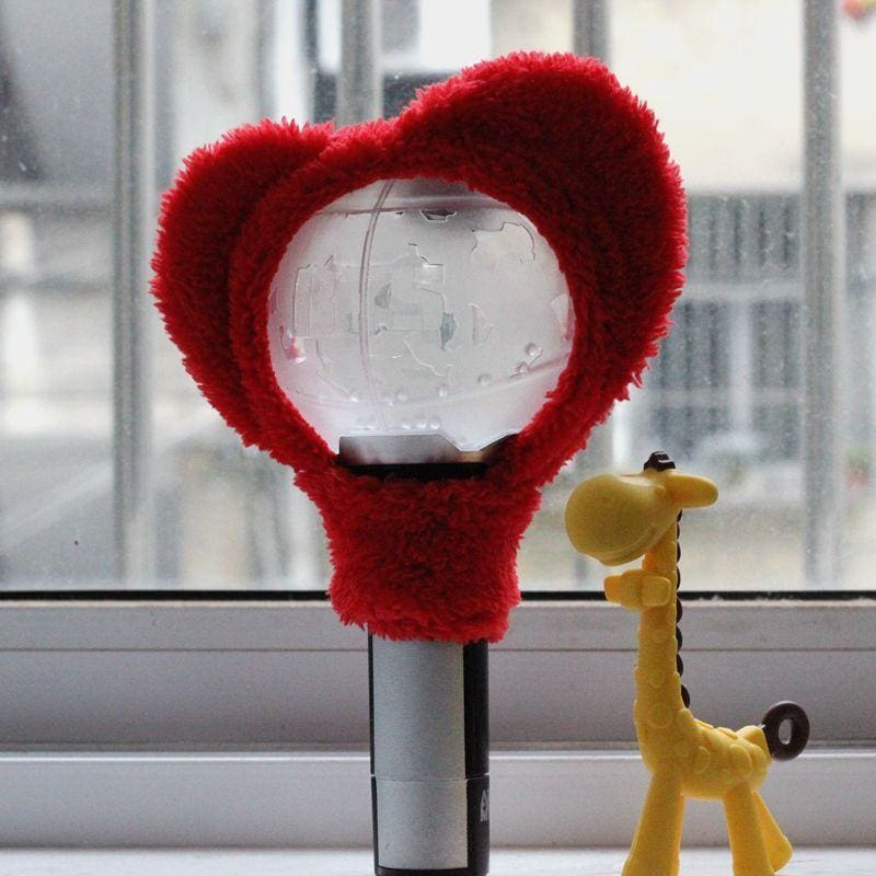 a red and white teddy bear sitting in front of a window
