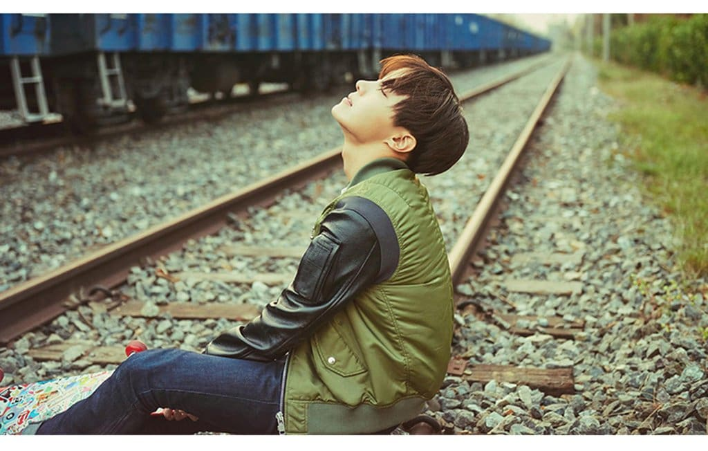 a little girl sitting on a train track