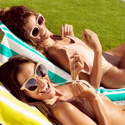 Two women lounging with dental floss