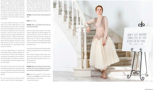 a brunette with shorter hair wearing a beige dress is standing next to the staircase