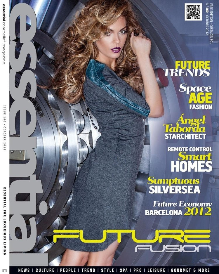Essential magazine. A Brunette with curly long hair wearing a grey-ish blue dress