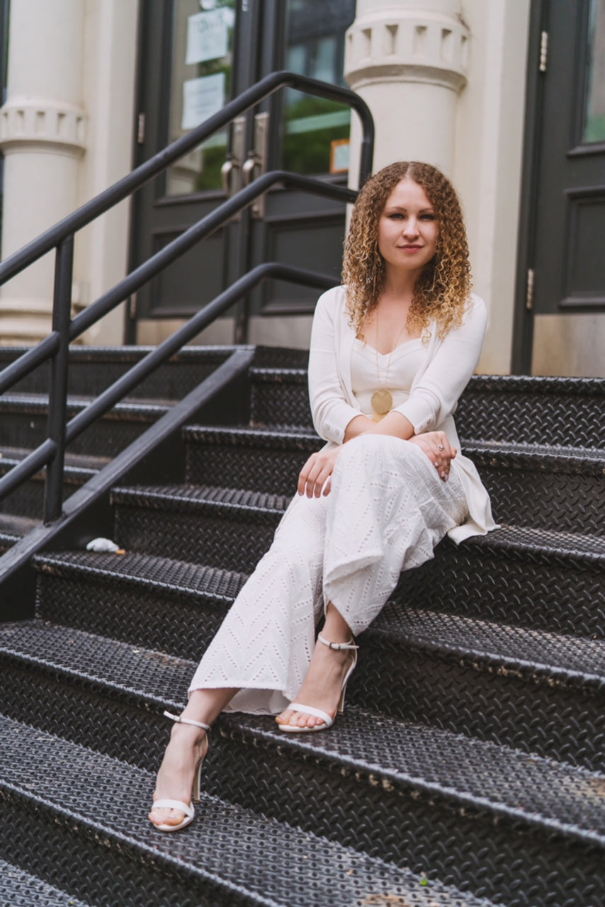A blonde girl wearing a white dress sitting on steps, after hiring a stylist