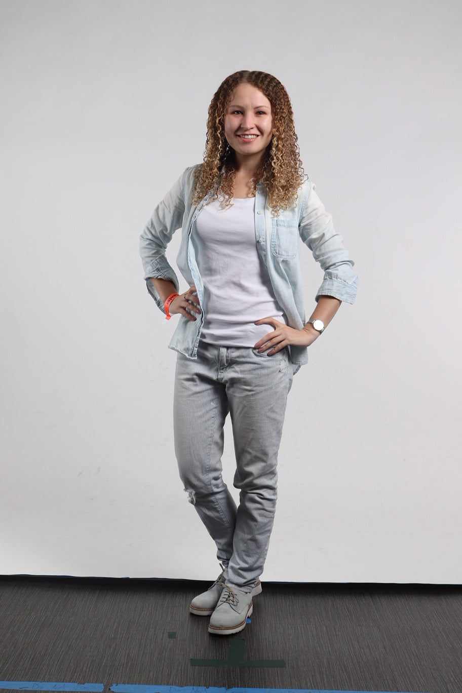 A blonde girl wearing grey pants, white shirt and light jacket, before hiring a stylist