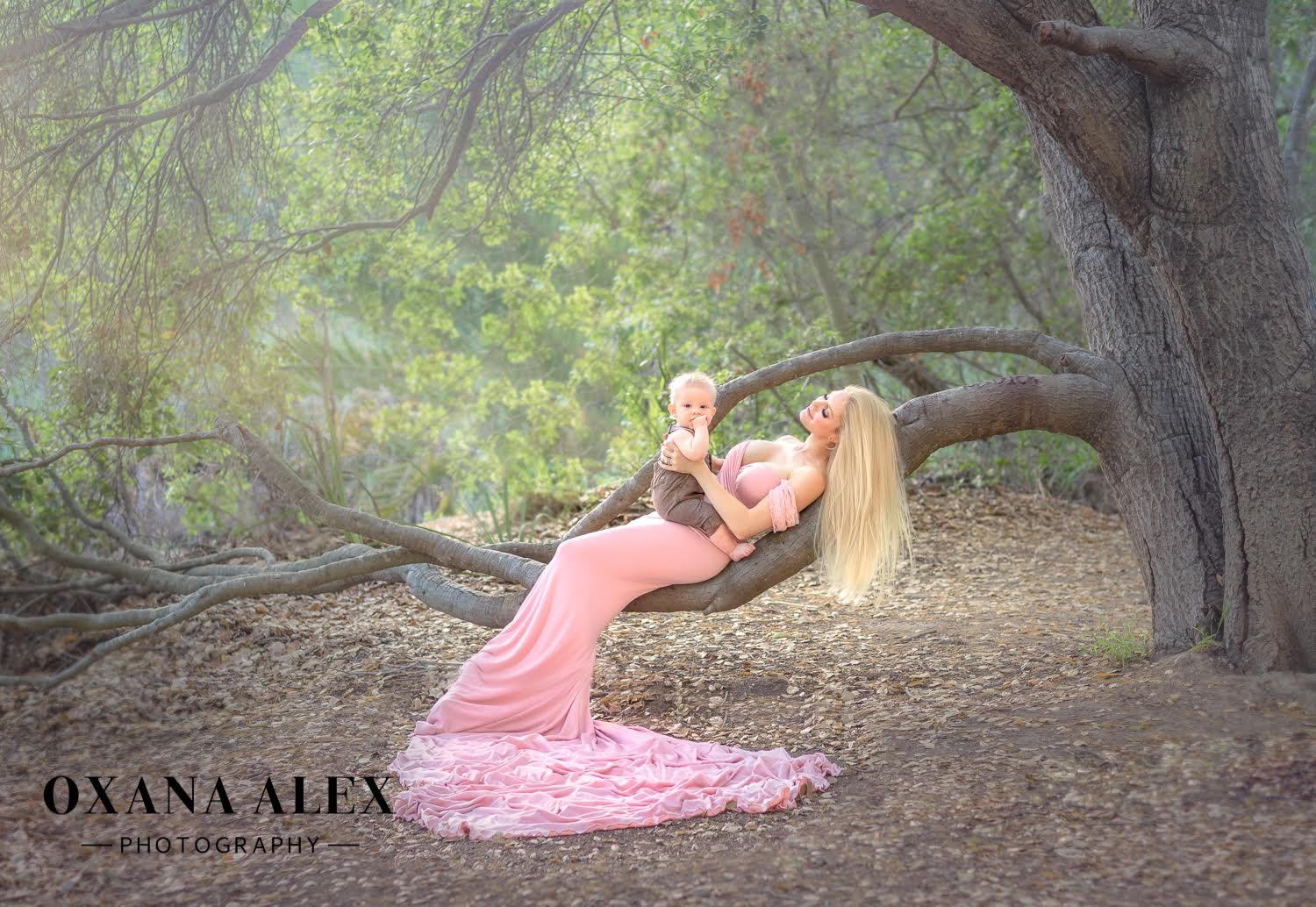 a blonde girl wearing a long pink dress lying on a branch of a tree and holding a baby