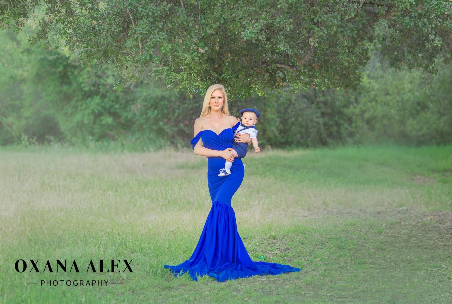 a blonde girl wearing a dark blue dress holding a baby having trees as the background