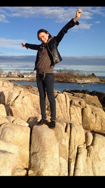 A girl standing on rocks wearing a black leather coat before hiring a stylist
