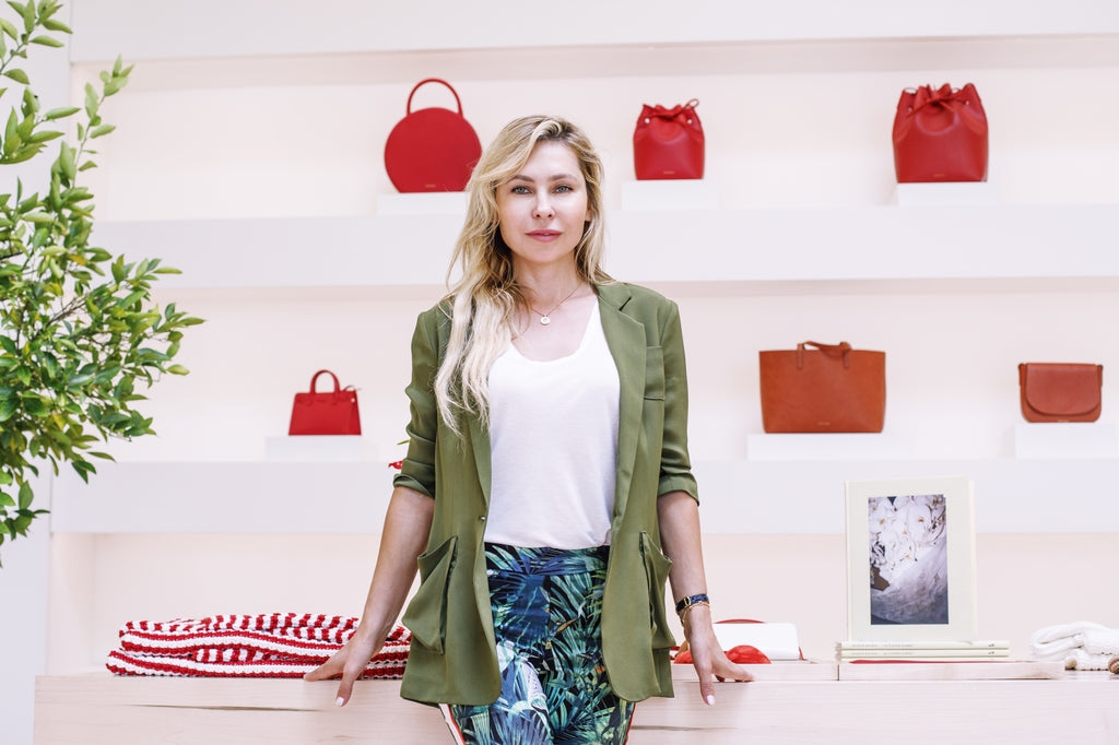 Natalia Naila standing next to a pink table with a lot of red bags of different kinds sitting on the wall
