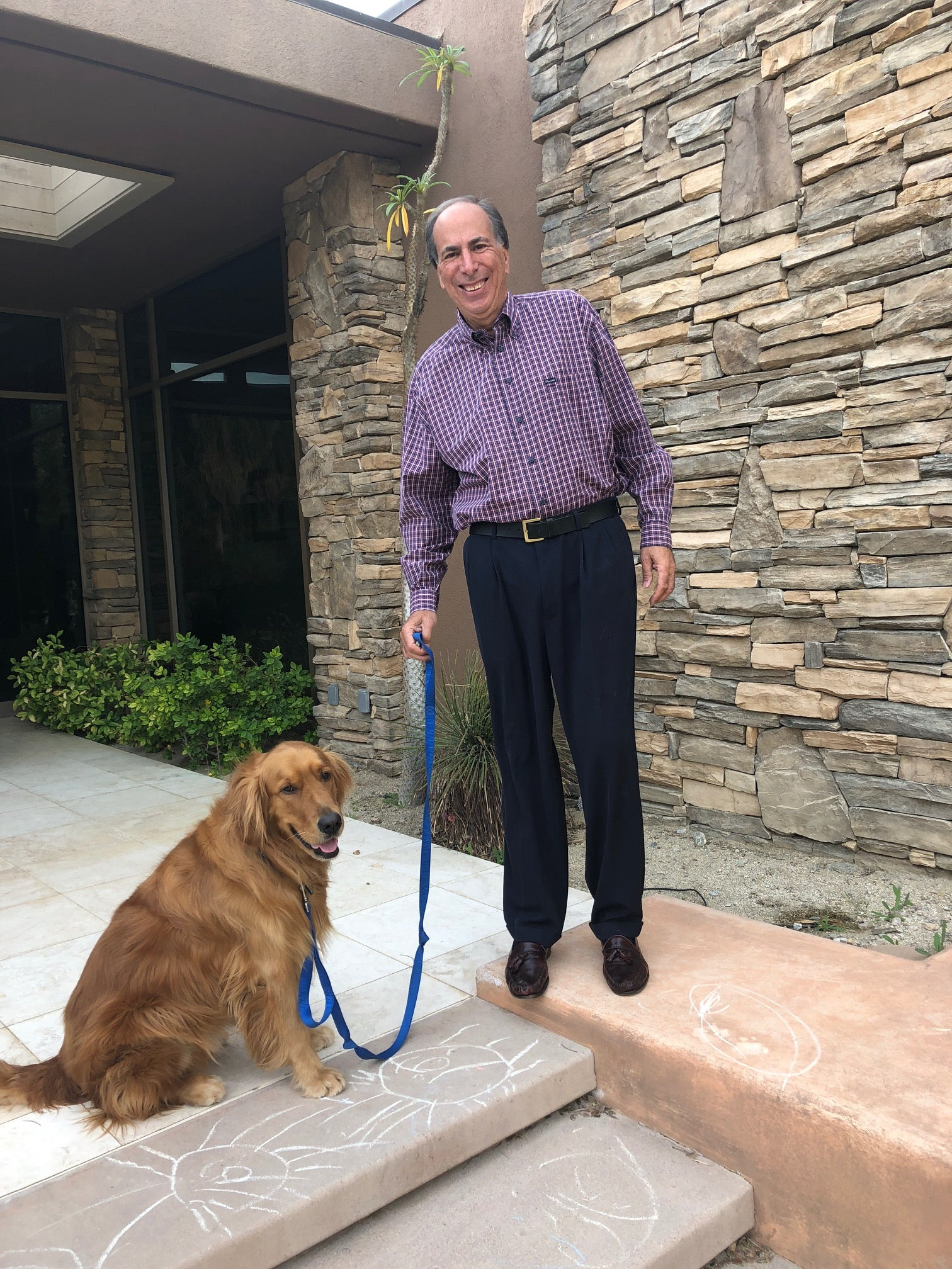 An older guy wearing a shirt and trousers standing next to his dog before he hired a stylist