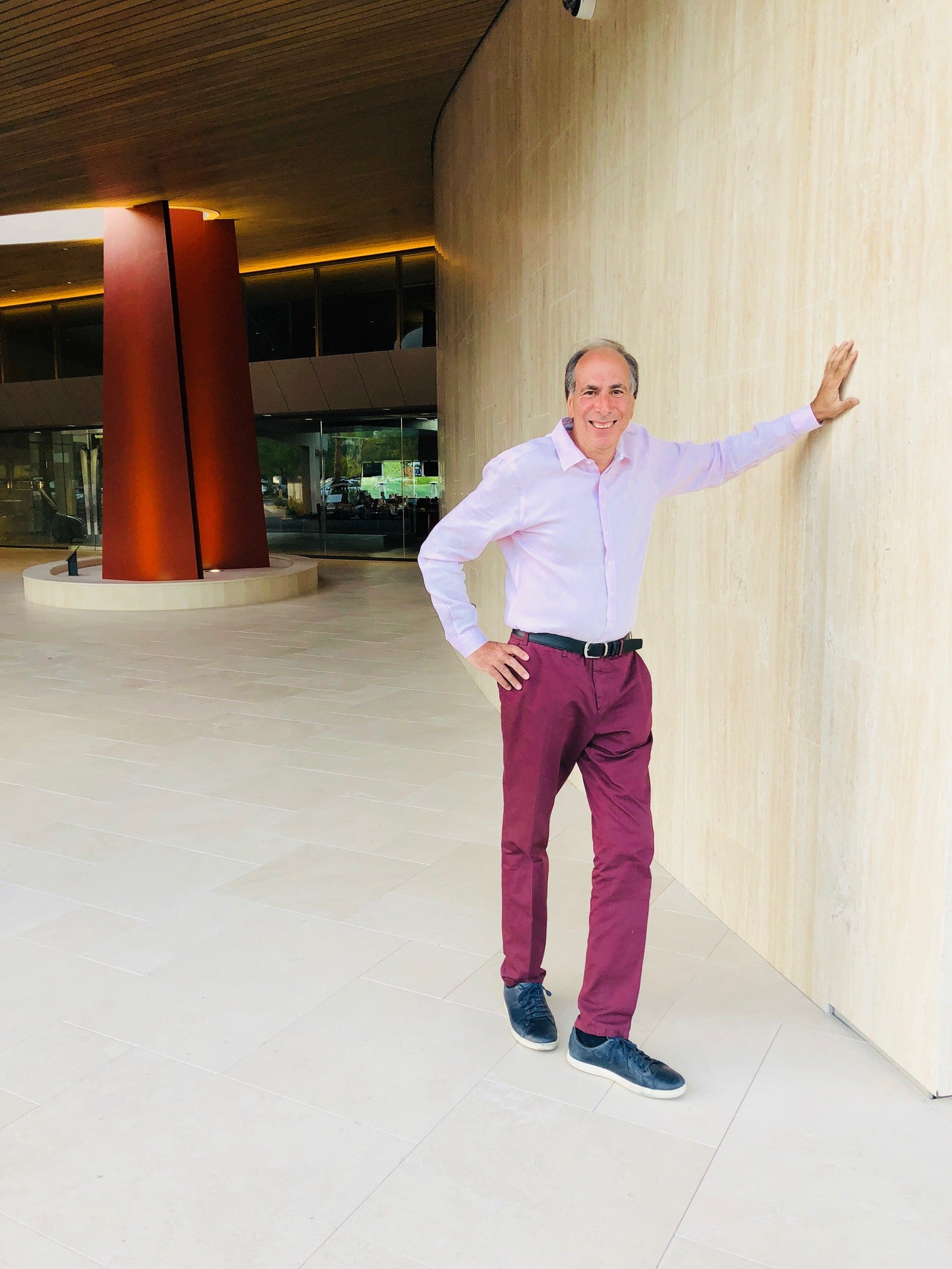 An older guy standing next to the wall wearing a shirt and pink trousers after hiring a stylist