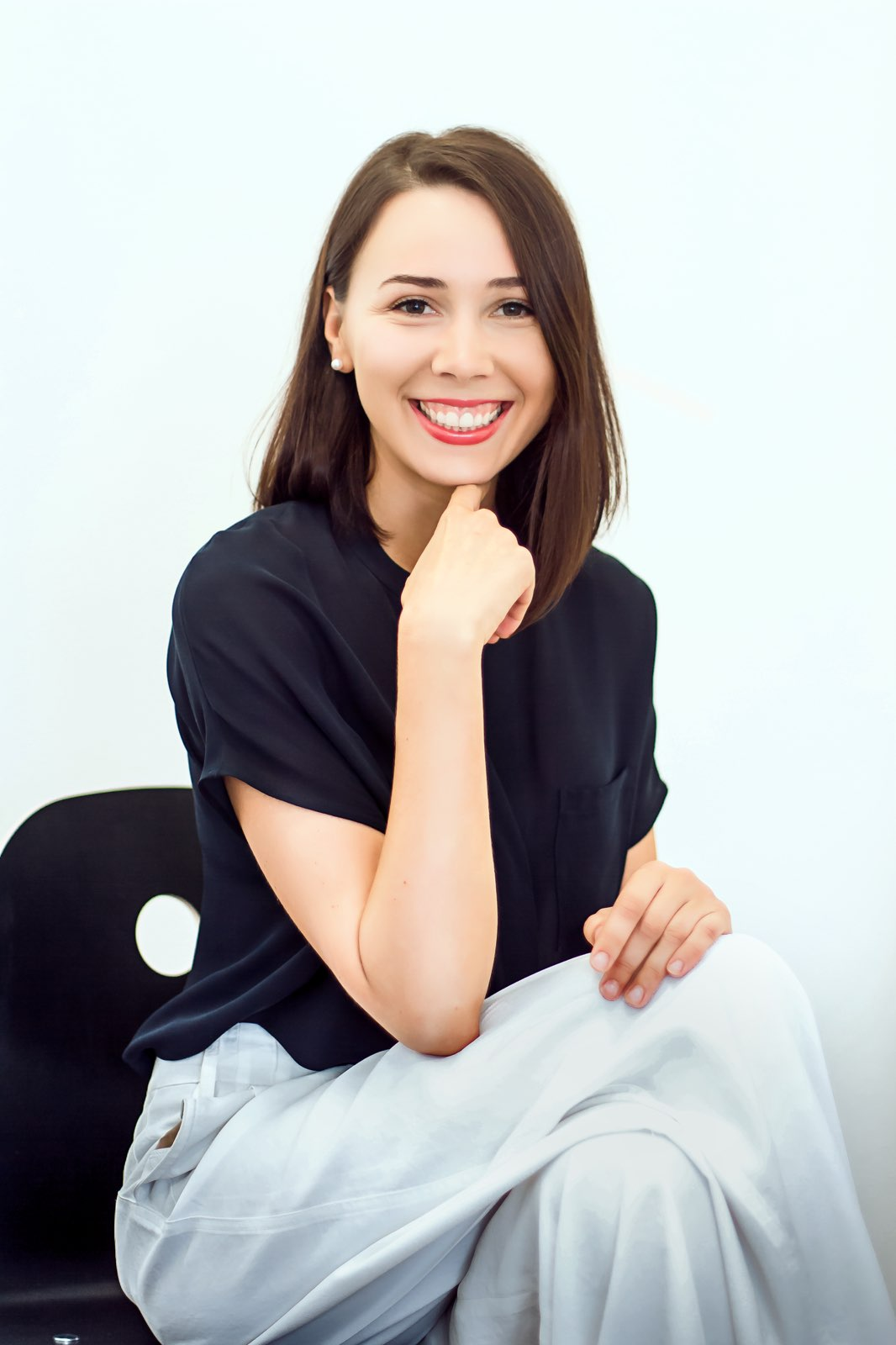 A brunette girl smiling, wearing dark blue shirt and grey pants, after hiring a stylist