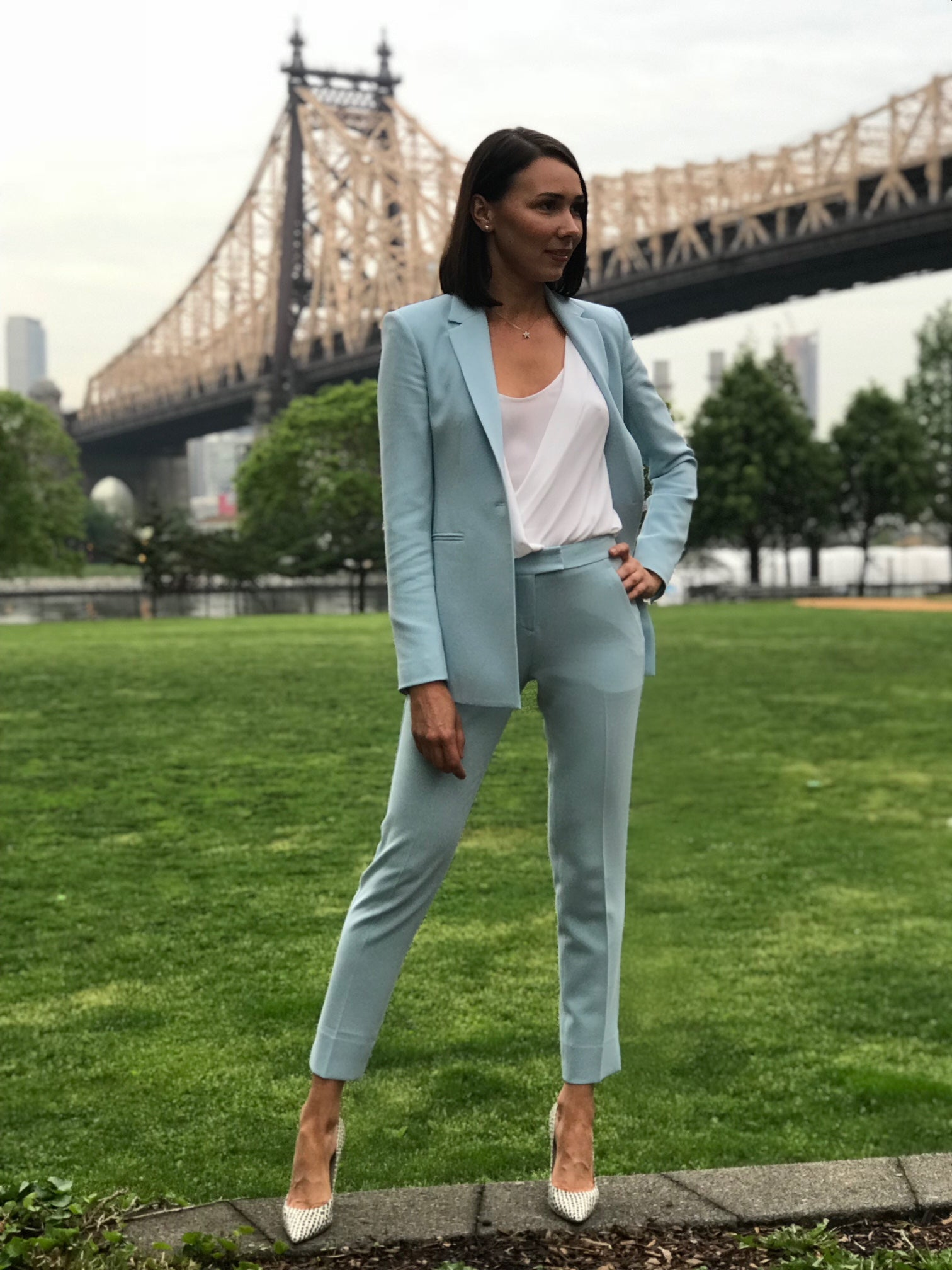 A brunette girl standing on a sidewalk wearing a teal suit
