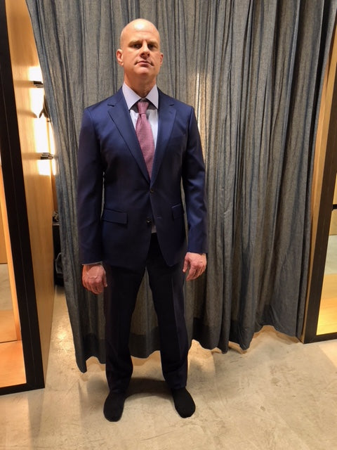 A bald man wearing a blue suit and a tie in a dressing room after hiring a stylist