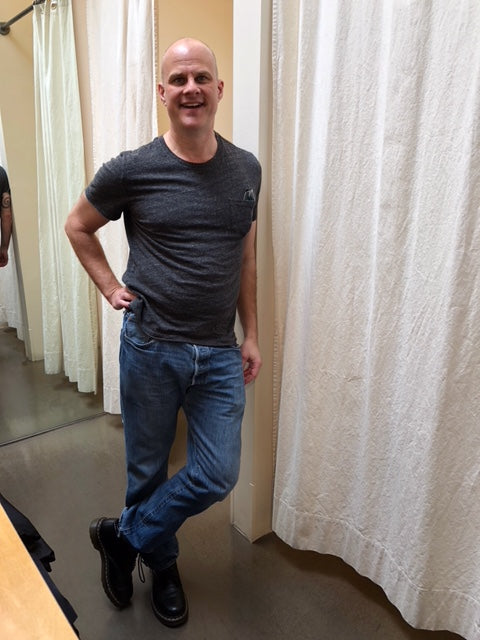 A bald man wearing a t-shirt and jeans before he hired a stylist