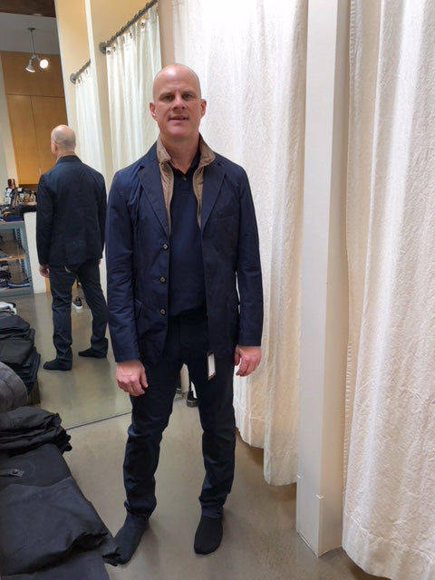 A bald man wearing a blue coat in a dressing room after hiring a stylist