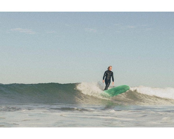 Ambassador Bjorn Haeck standing tall on a longboard surfboard on a small wave in sunny France, wearing wetsuit