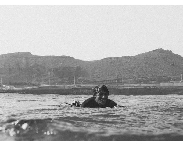 surfer smiling in the water, black and white image of surfing dude at the coastline