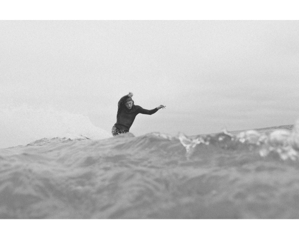 black and white photo of surfer surfing a big wave while doing a trick on the wave