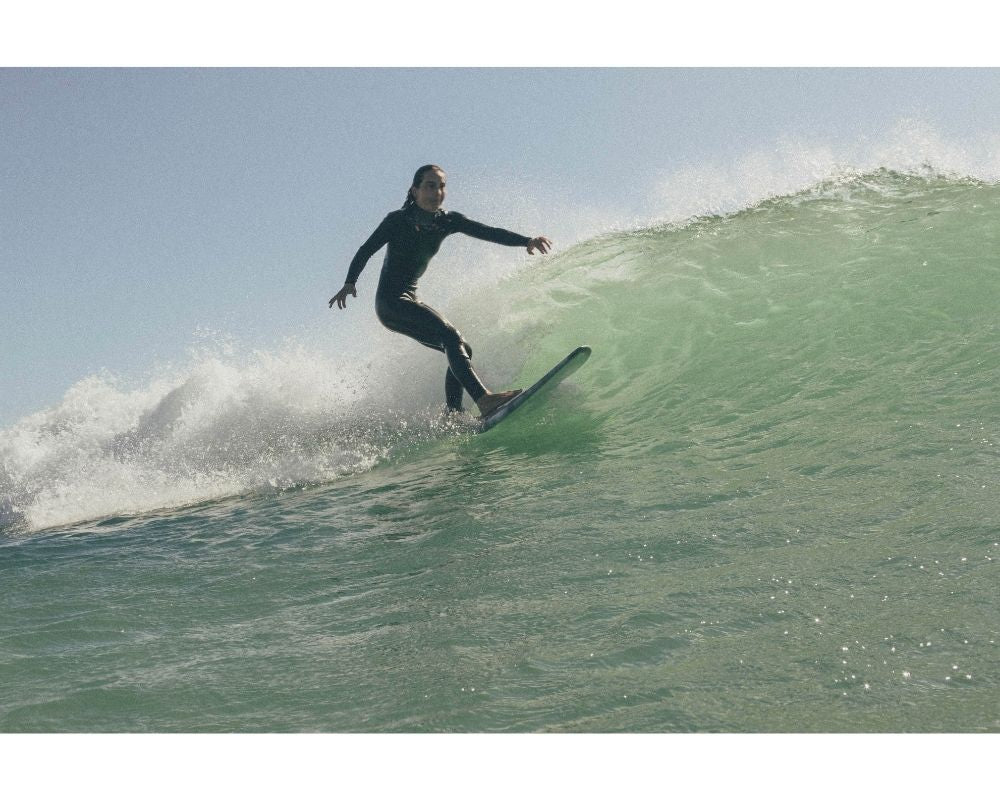 colour picture of woman surfing in France, big wave with her shortboard in a wetsuit