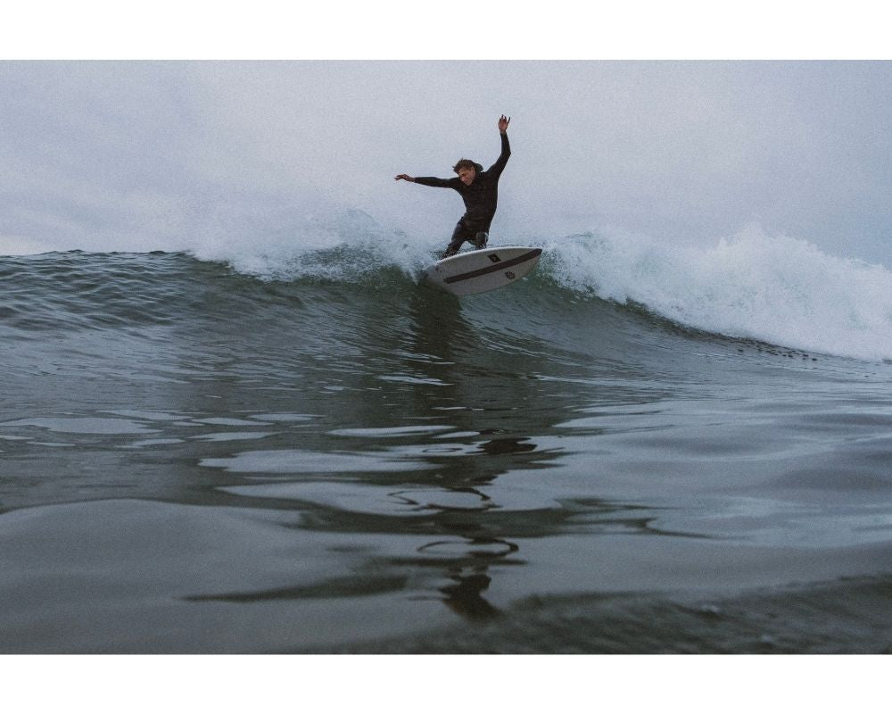 Our ambassador Boy surfing on a small wave with his performance shortboard