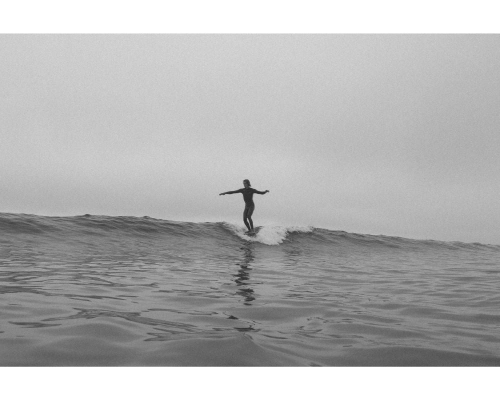 black and white photo of our female ambassador surfing a small wave with her longboard in France