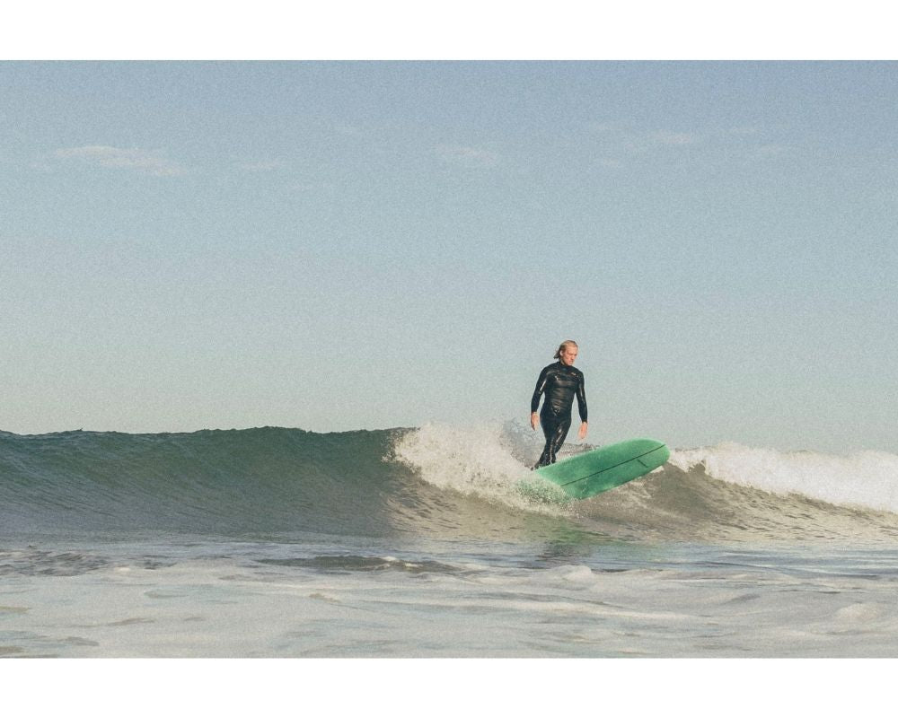photo of our surf photographer Bjorn standing tall on his longboard while surfing, green longboard dancing style in summer