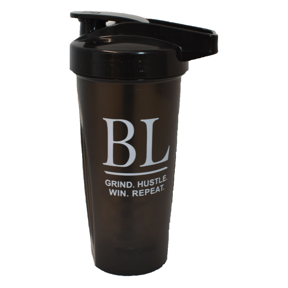 BLACKLABEL Supplements Performa shaker bottle with the lid on.  The shaker is black with light grey text that has large letters BL and GRIND HUSTLE WIN REPEAT below the letters.