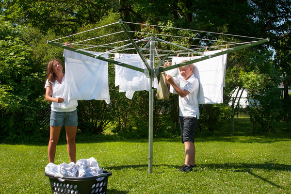 Mother and boy enjoying the sunshine while hanging laundry.