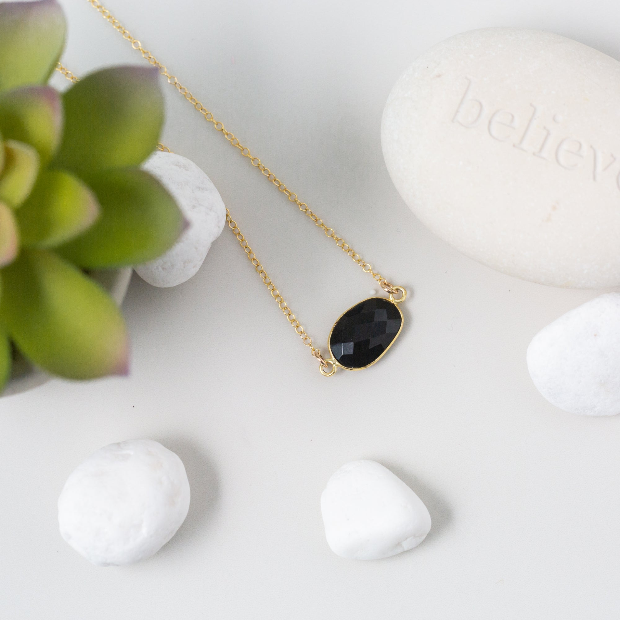 Oval-shaped Spinel and Gold Necklace 'I Am Badass' Flat Lay with Plant and White Stones Photo by Asha Blooms
