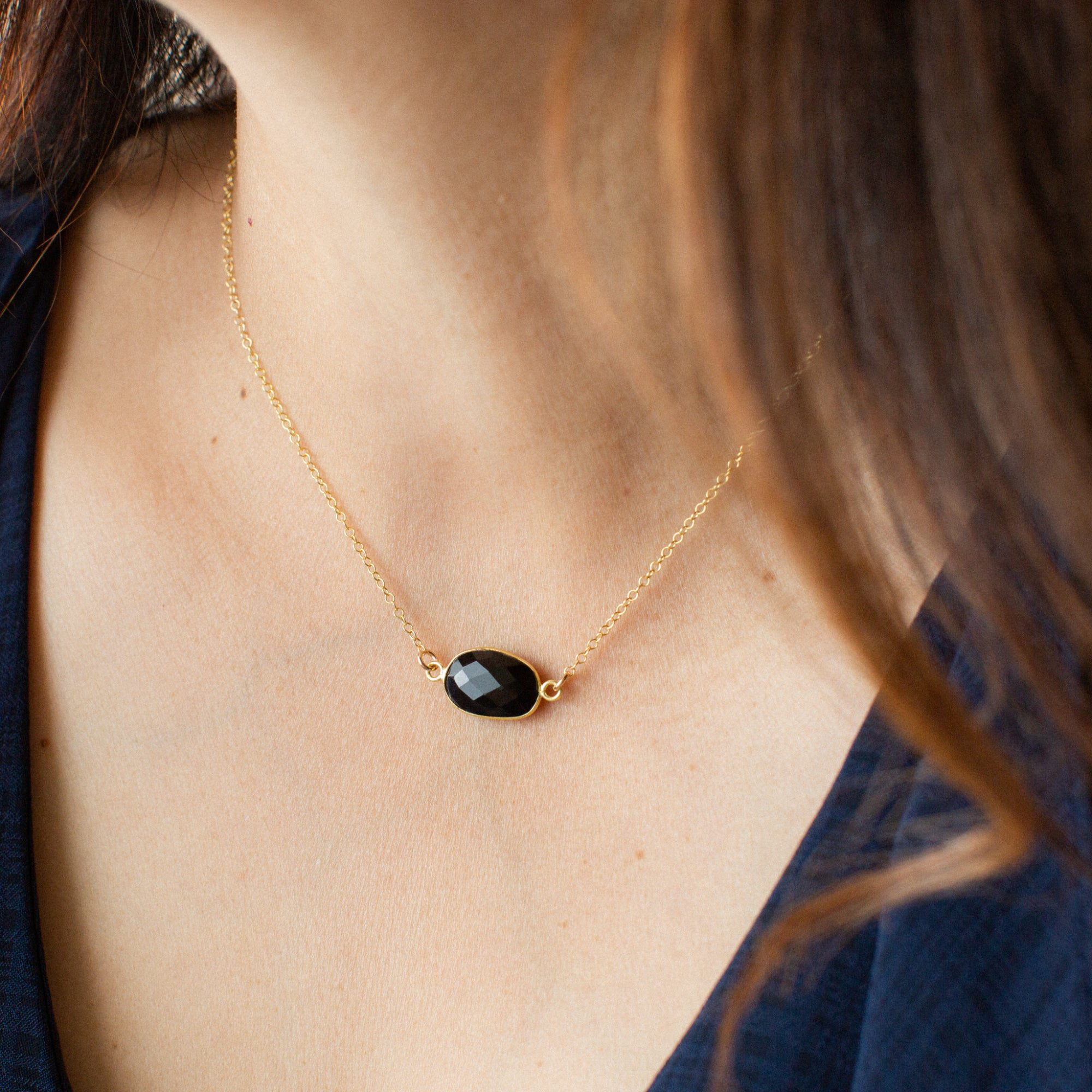 Close-up of Woman in Blue Shirt Wearing Oval-shaped Spinel and Gold Necklace 'I Am Badass' Model Photo by Asha Blooms