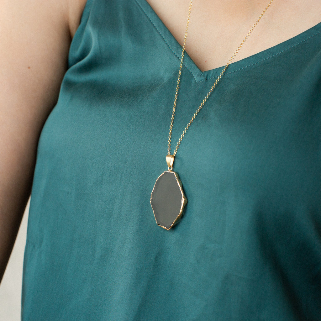 Close-up of Woman in Green Shirt Wearing Slice-shaped Smoky Quartz and Gold or Silver Long Necklace 'I Am Brave' Model Photo by Asha Blooms