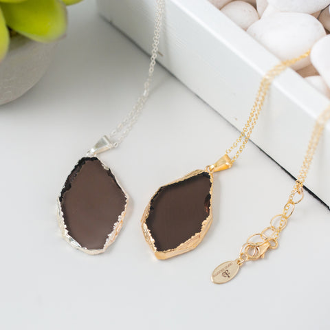 Slice-shaped Smoky Quartz and Gold or Silver Long Necklace 'I Am Brave' Flat Lay with Plant and White Stones Photo by Asha Blooms