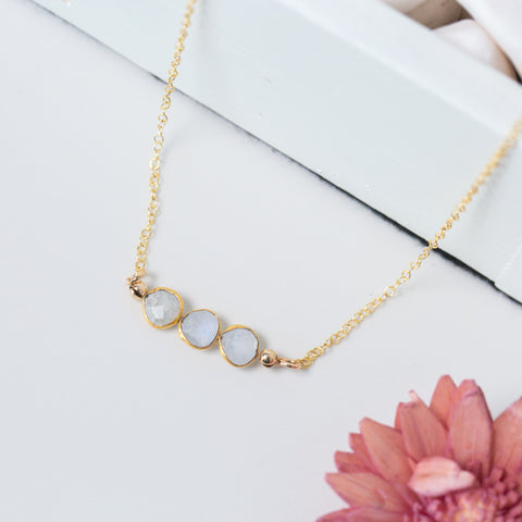 Three Small Circle-shaped Stones Side-by-side in Moonstone and Gold Necklace 'I Am Grateful' Flat Lay with Pink Flower Photo by Asha Blooms