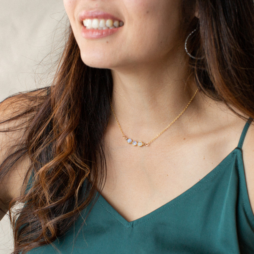 Woman in Green Shirt Smiling and Wearing Three Small Circle-shaped Stones Side-by-side in Moonstone and Gold Necklace 'I Am Grateful' Model Photo by Asha Blooms