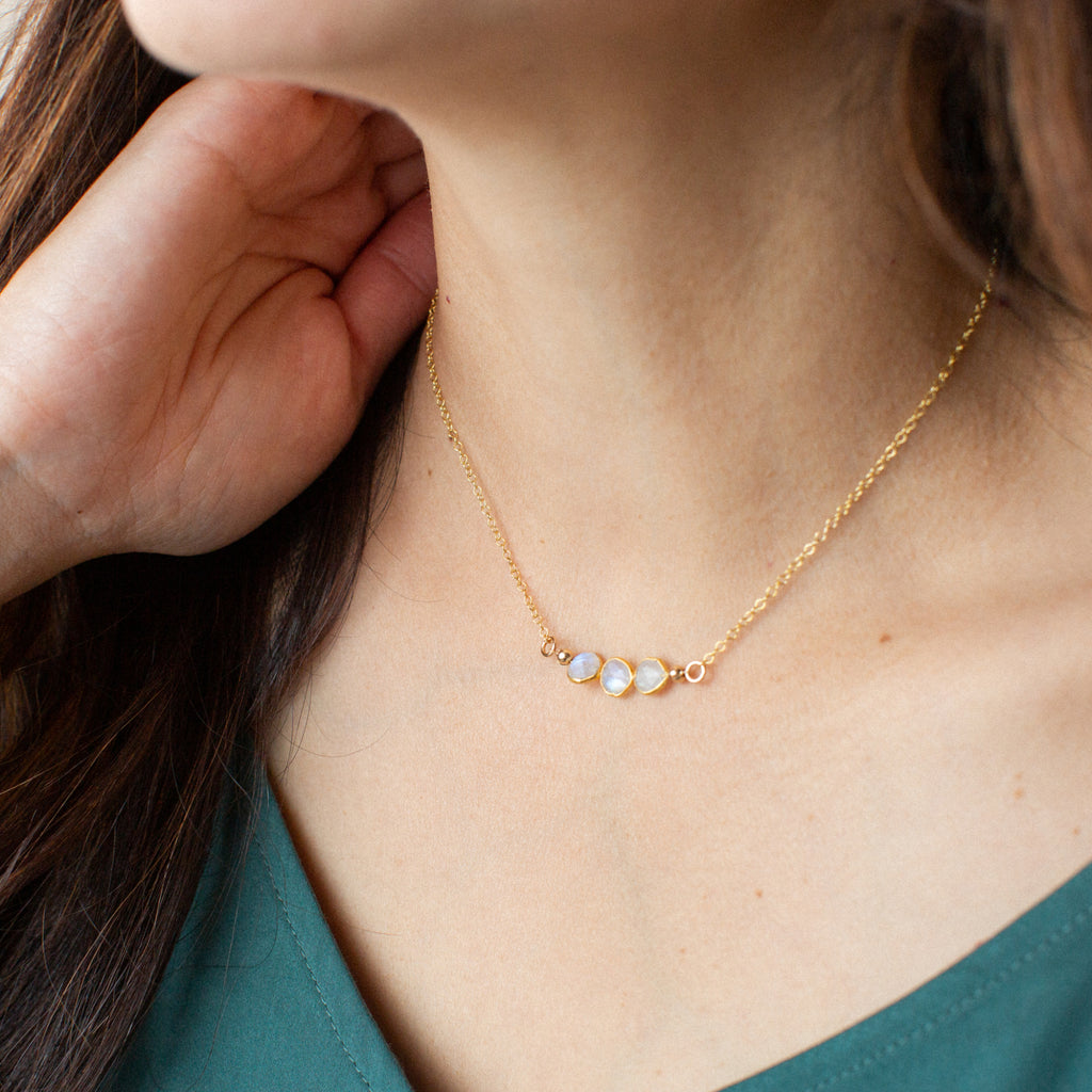 Close-up of Woman in Green Shirt Wearing Three Small Circle-shaped Stones Side-by-side in Moonstone and Gold Necklace 'I Am Grateful' Model Photo by Asha Blooms