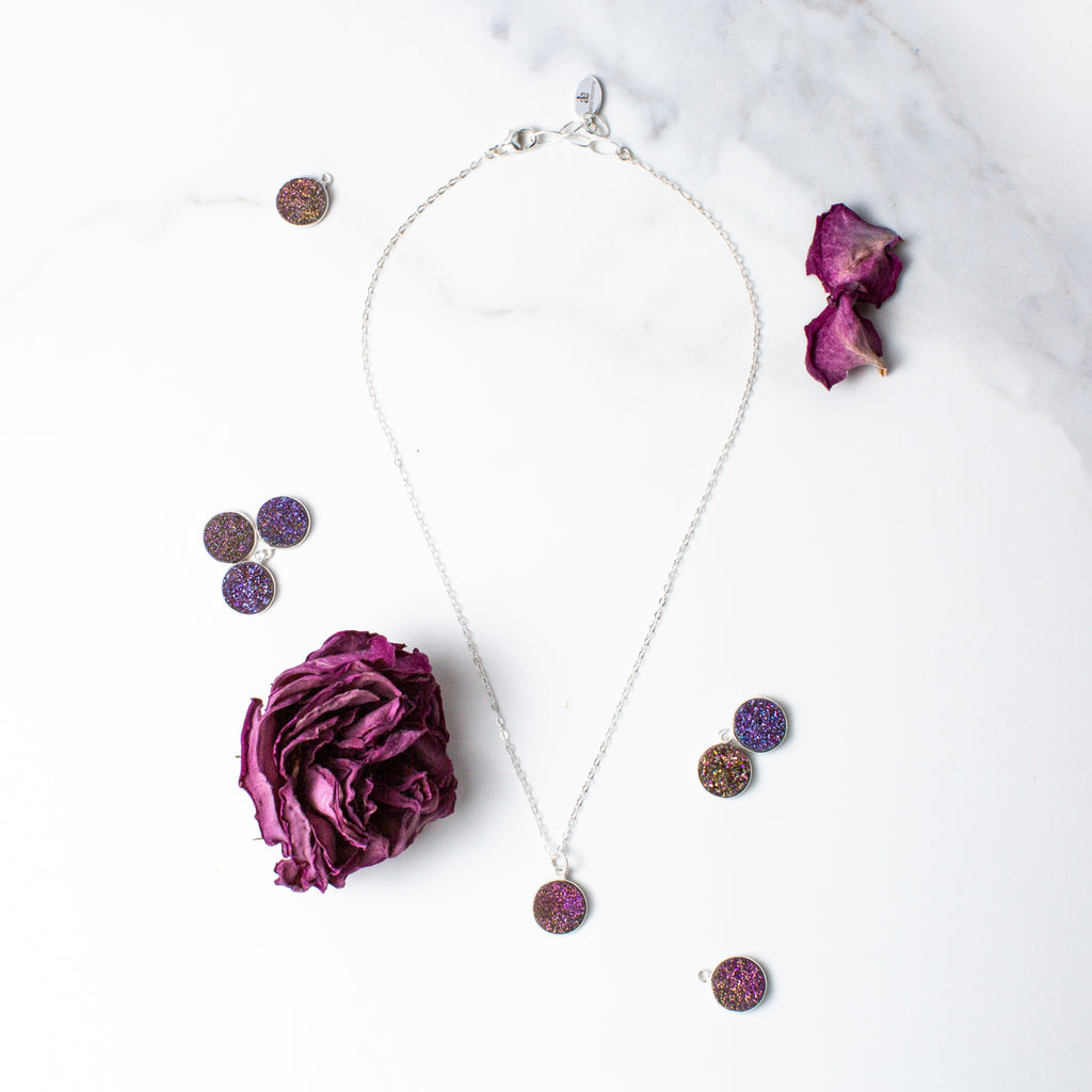 Circular Purple Druzy and Silver Necklace 'I Am Happy' Flat Lay with Purple Flower Petals Photo by Asha Blooms