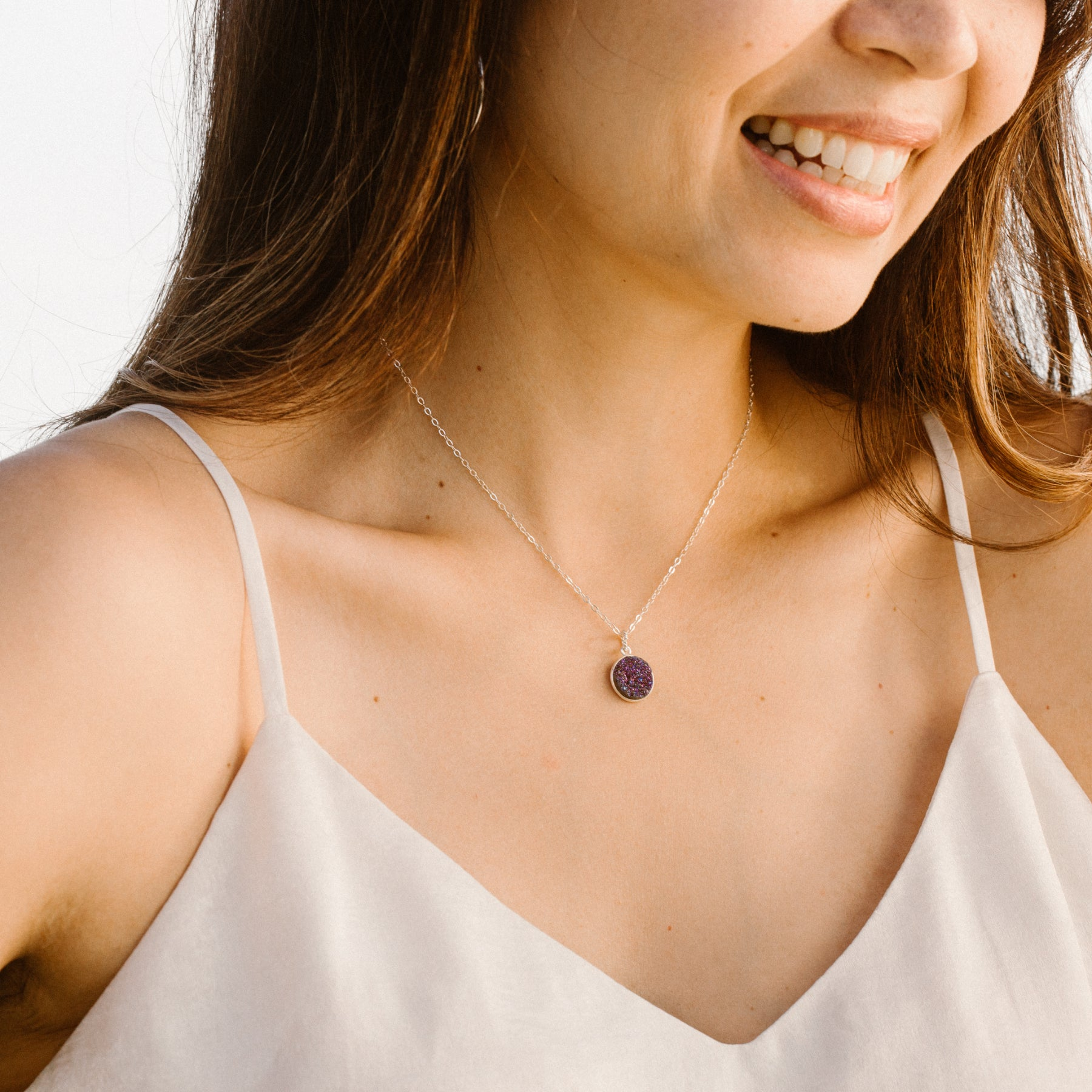 Woman in White Shirt Smiling and Wearing Circular Purple Druzy and Silver Necklace 'I Am Happy' Model Photo by Asha Blooms
