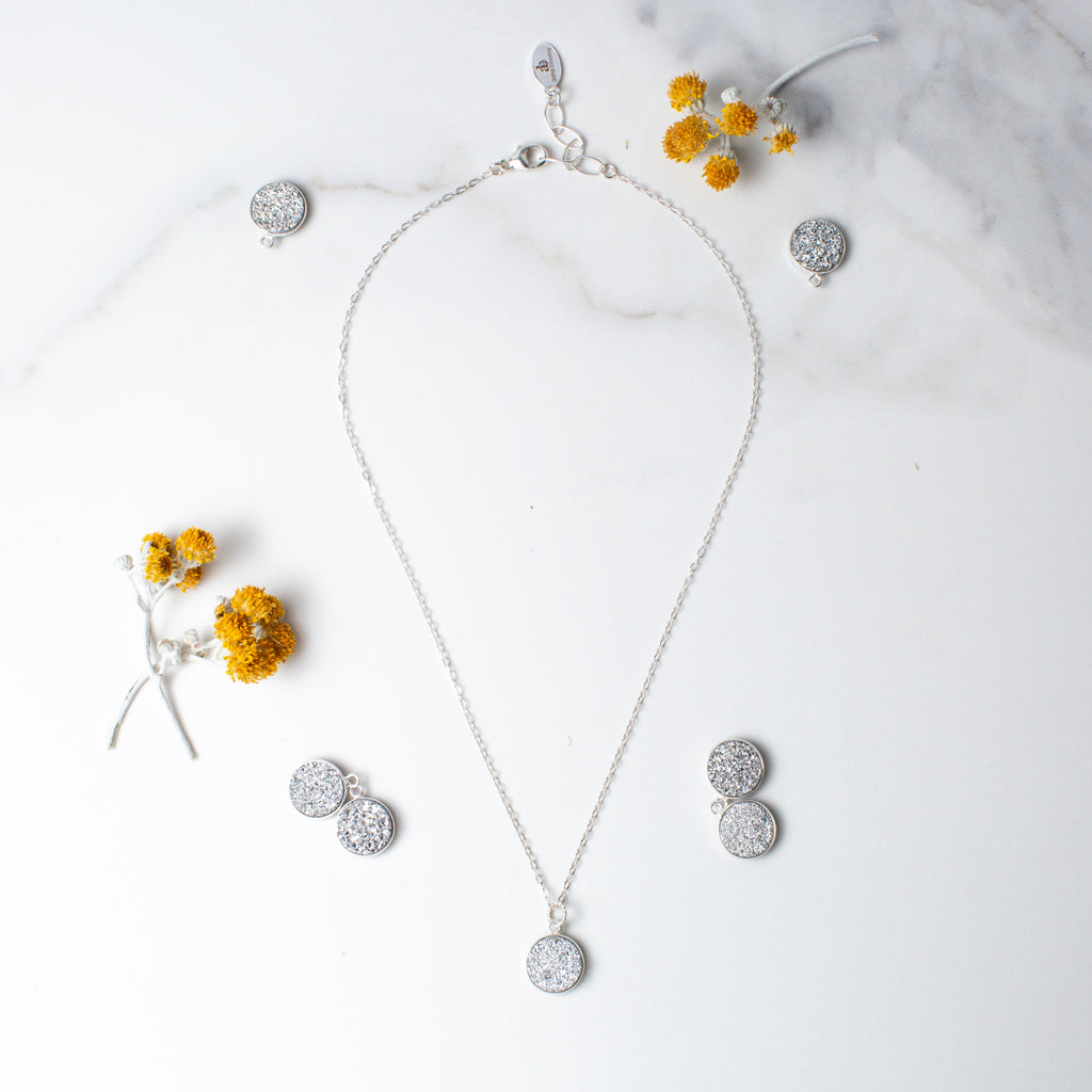 Circular Silver Druzy and Silver Necklace 'I Am Happy' Flat Lay with Yellow Flowers Photo by Asha Blooms