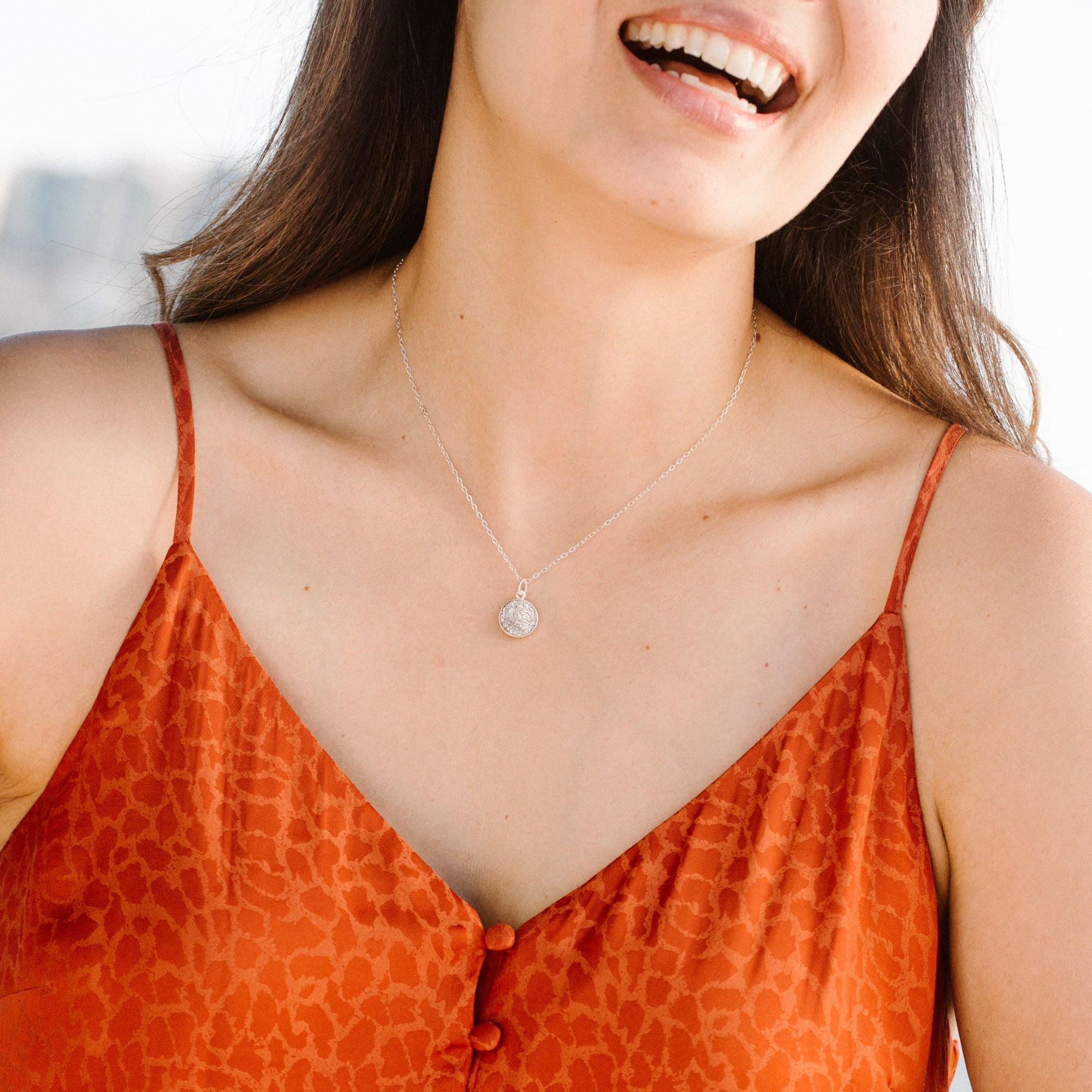 Woman in Orange Shirt Smiling and Wearing Circular Silver Druzy and Silver Necklace 'I Am Happy' Model Photo by Asha Blooms