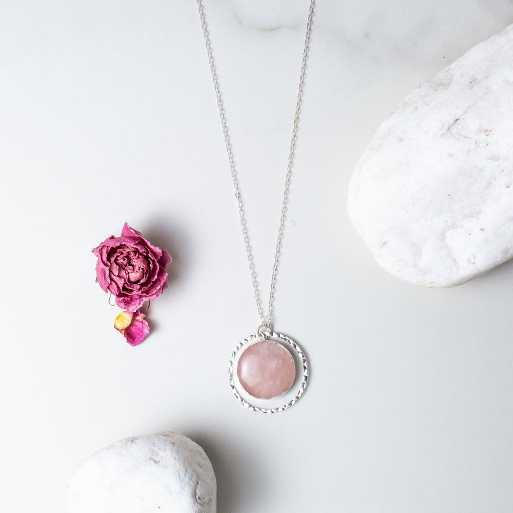 Circular Rose Quartz and Silver Hammered Circle Necklace 'I Am Loved' Flat Lay with Pink Flower Petals and White Stones Photo by Asha Blooms