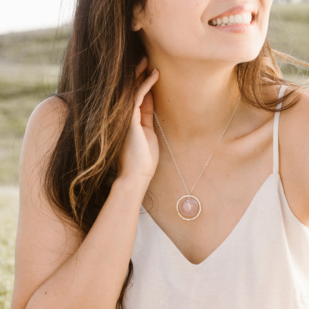 Woman in White Shirt Smiling and Wearing Circular Rose Quartz and Silver Hammered Circle Necklace 'I Am Loved' Model Photo by Asha Blooms