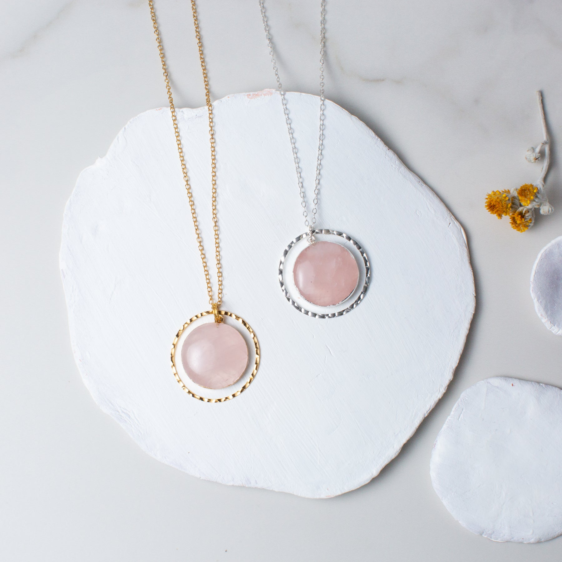 Circular Rose Quartz and Gold or Silver Hammered Circle Necklace 'I Am Loved' Flat Lay with Yellow Flowers and White Stones Photo by Asha Blooms