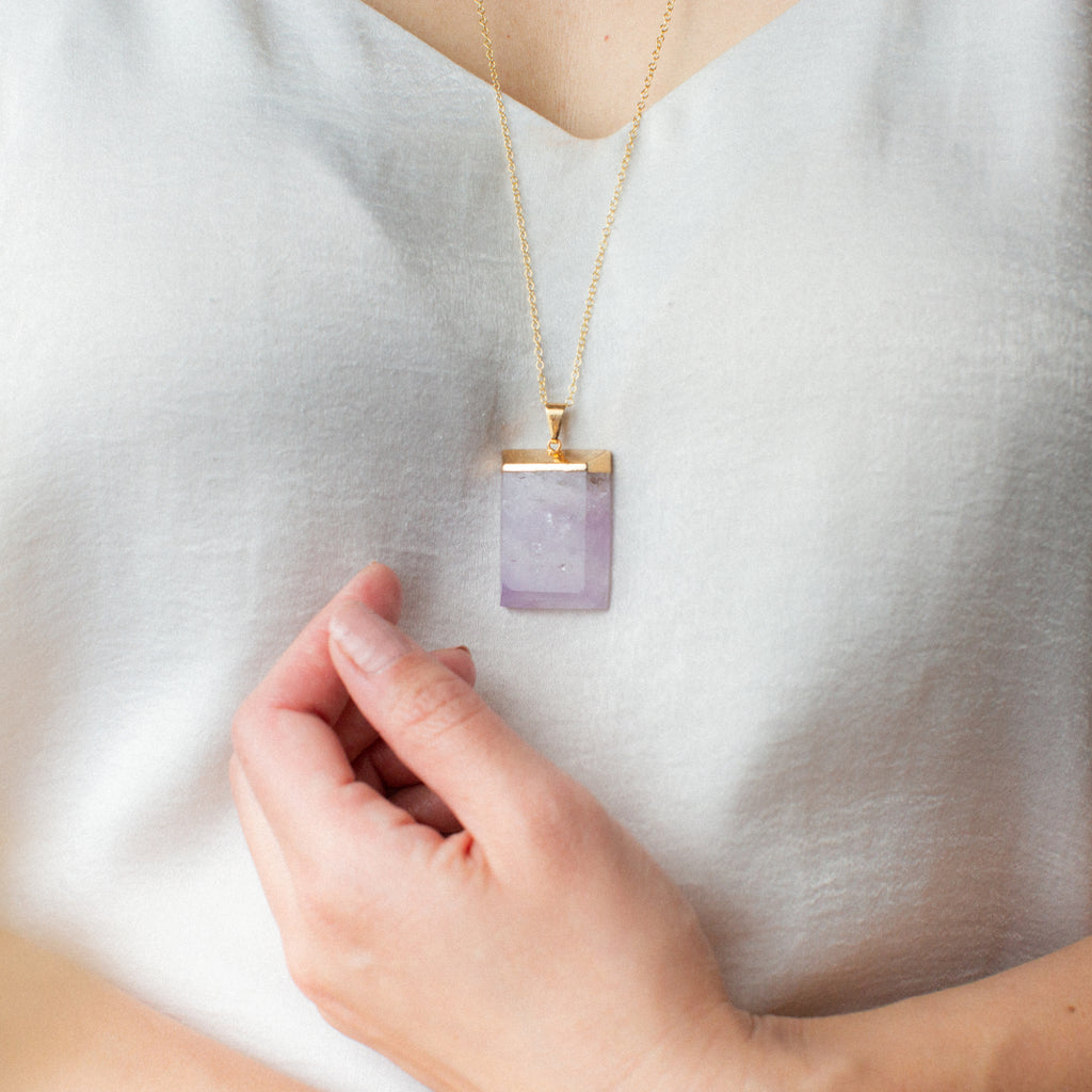 Close-up of Woman in White Shirt Wearing Rectangular Purple Amethyst and Gold Long Necklace 'I Am Protected' Model Photo by Asha Blooms